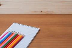 Farbige Bleistifte mit einem Notizbuch auf dem Tisch Lizenzfreies Stockfoto