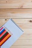 Farbige Bleistifte mit einem Notizbuch auf dem Tisch Lizenzfreie Stockbilder