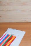 Farbige Bleistifte mit einem Notizbuch auf dem Tisch Lizenzfreie Stockfotos