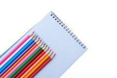 Farbige Bleistifte mit einem Notizbuch auf weißem Hintergrundabschluß oben Stockbild