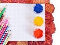 Farbige Bleistifte mit einem Notizbuch und Herbstlaub Lizenzfreie Stockbilder