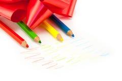 Farbige Bleistifte mit einem roten Bogen lokalisiert Stockbilder