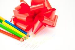 Farbige Bleistifte mit einem roten Bogen lokalisiert Stockfoto