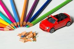 Farbige Bleistifte mit Schnitzeln und kleines rotes Spielzeugauto auf weißem Holztisch Lizenzfreies Stockfoto