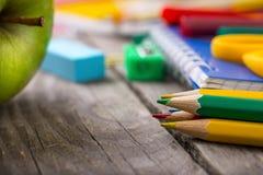 Farbige Bleistifte mit Schulbedarf und grünem Apfel Lizenzfreie Stockfotografie