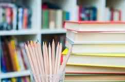Farbige Bleistifte mit Stapel von Büchern im Hintergrund Stockfoto