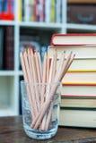 Farbige Bleistifte mit Stapel von Büchern im Hintergrund Stockfotos
