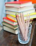Farbige Bleistifte mit Stapel von Büchern im Hintergrund Stockbild