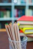 Farbige Bleistifte mit Stapel von Büchern im Hintergrund Lizenzfreies Stockbild