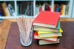 Farbige Bleistifte mit Stapel von Büchern mit farbigen Abdeckungen Lizenzfreie Stockfotos