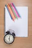 Farbige Bleistifte mit Wecker auf leerem Notizbuch Lizenzfreie Stockfotografie