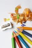 Farbige Bleistifte, Schnitzel und Bleistiftspitzer Lizenzfreie Stockfotografie