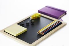 Farbige Bleistifte, schwarzes Brett, Mappenclip, Notizbuch und memopads Lizenzfreie Stockfotos