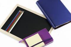 Farbige Bleistifte, schwarzes Brett, Notizbücher und memopad Stockbild