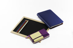 Farbige Bleistifte, schwarzes Brett, Notizbücher und memopads Lizenzfreie Stockfotos