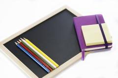Farbige Bleistifte, schwarzes Brett, Notizbuch und memopad Stockfotos