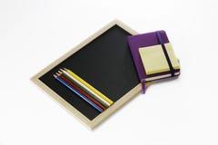 Farbige Bleistifte, schwarzes Brett, Notizbuch und memopad Stockbilder