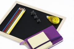 Farbige Bleistifte, schwarzes Brett, Notizbuch und memopad Lizenzfreies Stockfoto