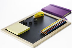 Farbige Bleistifte, schwarzes Brett, Notizbuch und memopad Stockfotografie
