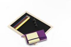 Farbige Bleistifte, schwarzes Brett, Notizbuch und memopads Stockfotos