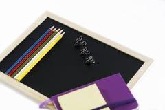 Farbige Bleistifte, schwarzes Brett, Notizbuch und memopads Lizenzfreie Stockfotografie