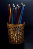 Farbige Bleistifte sind durch ein Weidenglas sichtbar Stockfoto
