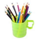 Farbige Bleistifte sind in einem grünen Cup Lizenzfreies Stockbild