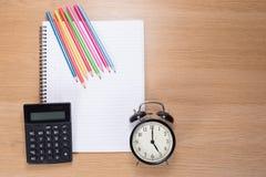 Farbige Bleistifte, Uhr und Taschenrechner auf Notizbuch Stockfotos