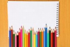 Farbige Bleistifte und überprüftes Notizbuch Lizenzfreies Stockbild