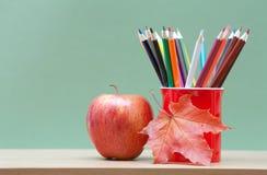 Farbige Bleistifte und Apfel Stockbild