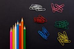 Farbige Bleistifte und Büroklammern auf einem schwarzen Hintergrund Stockfoto