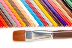 Farbige Bleistifte und Bürste auf weißem Hintergrund Lizenzfreie Stockfotografie