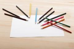 farbige Bleistifte und Blatt des Weißbuches auf Schreibtisch Stockfoto