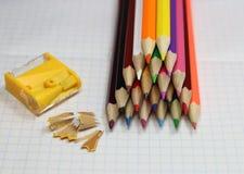 Farbige Bleistifte und Bleistiftspitzer Stockbild