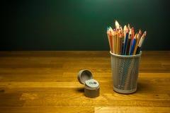 Farbige Bleistifte und Bleistiftspitzer auf dem Tisch Stockfoto