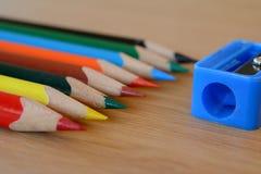 Farbige Bleistifte und Bleistiftspitzer auf Holztisch Lizenzfreie Stockfotografie