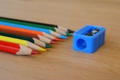Farbige Bleistifte und Bleistiftspitzer auf Holztisch Stockfotografie