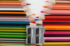Farbige Bleistifte und Bleistiftspitzer auf weißem Hintergrund Stockbild