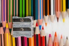 Farbige Bleistifte und Bleistiftspitzer auf weißem Hintergrund Lizenzfreie Stockfotos