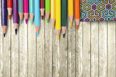 Farbige Bleistifte und Buch auf dem Tisch Lizenzfreie Stockbilder