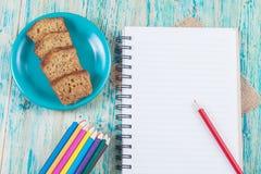 Farbige Bleistifte und Buchanmerkung über Schreibtisch Lizenzfreie Stockfotografie