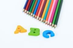 Farbige Bleistifte und Buchstaben des Alphabetes auf einem weißen Hintergrund Foto mit Kopienraum Stockfotografie