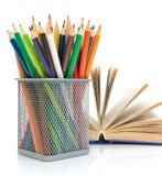 Farbige Bleistifte und ein Buch auf einem weißen Hintergrund Lizenzfreie Stockbilder