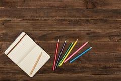 Farbige Bleistifte und ein Notizblock auf einem hölzernen Hintergrund Kopieren Sie Platz Stockfotografie
