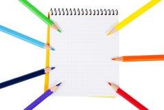 Farbige Bleistifte und ein Notizbuch Stockbild