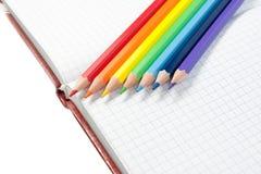 Farbige Bleistifte und ein Notizbuch Lizenzfreies Stockfoto