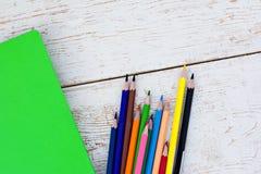 Farbige Bleistifte und ein Notizbuch Stockfotos