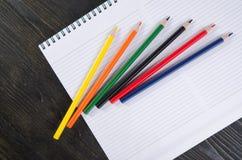 Farbige Bleistifte und ein Notizbuch Stockbilder