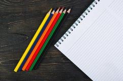 Farbige Bleistifte und ein Notizbuch Stockfotografie