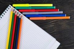 Farbige Bleistifte und ein Notizbuch Lizenzfreie Stockbilder